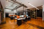 office with 4 white top desks, black chairs, polished floor boards and greenery
